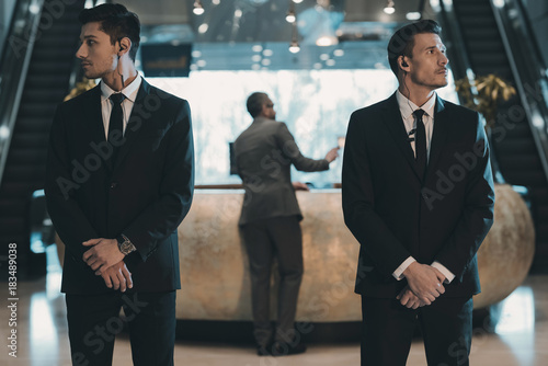 Fotomural  two bodyguards waiting for businessman standing at reception counter