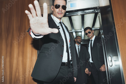 Fotomural bodyguard obstructing paparazzi when celebrity going into elevator