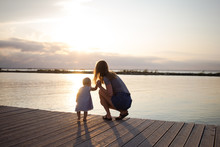 Mother And Daughter Walking On The Wooden Pier At Sunny Day, Happy Family On The Beach
