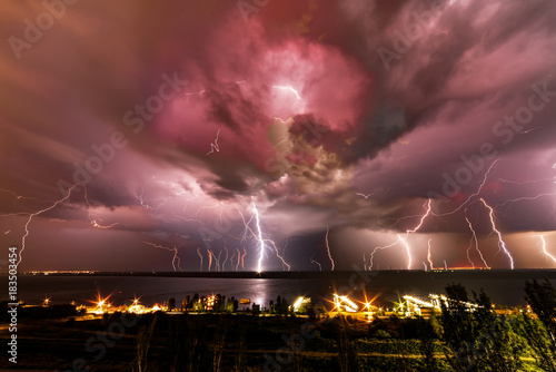 Fototapeta A huge number of bright and terrible lightning over the river.
