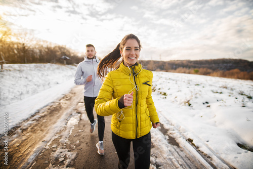 Foto op Canvas Jogging Beautiful happy active runner girl jogging with her personal handsome trainer on a snowy road in nature.