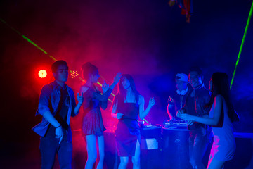 DJ playing music and Group of dancing friends enjoying night party. celebrating New Year together.
