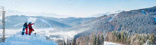 Winter panorama of the mountains landscape and forests in a white haze, two snowboarders resting on top of the mountain on a sunny winter day. Man pointing to the background copyspace snowboarding