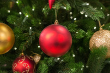 Red Bauble Hanging On A Christmas Tree Close Up