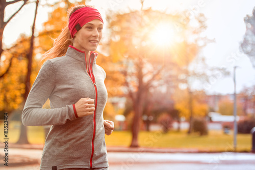 Foto op Canvas Jogging young beautiful caucasian woman jogging workout training. Autumn running fitness girl in city urban park environment with fall trees orange. Sunset or sunrise warm light. Sport activity in cold season
