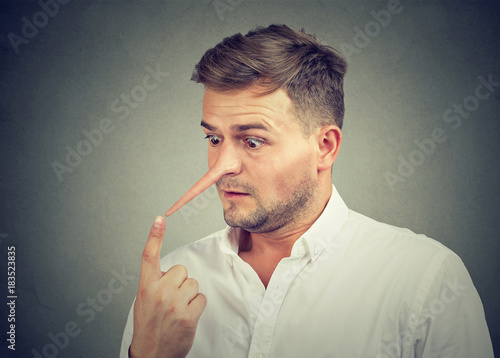 Worried shocked young man with long nose. Liar concept. Canvas Print
