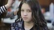 Professional hairdresser stylist curling up teen girl hair