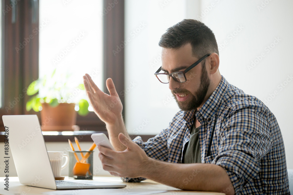 Fototapeta Confused bearded manager in glasses is angry because mobile phone is discharged. Millennial businessman in casual receiving bad news and spam in smartphone