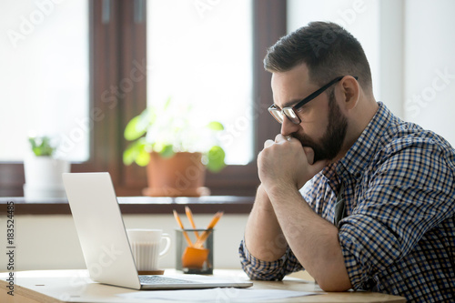 Young bearded manager working and reading data on laptop in home office Wallpaper Mural