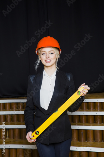Cuadros en Lienzo Beautiful blonde businesswoman with application tier at loft office in orange construction helmet and suit