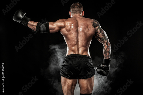 Photo Sportsman muay thai boxer fighting on black background with smoke