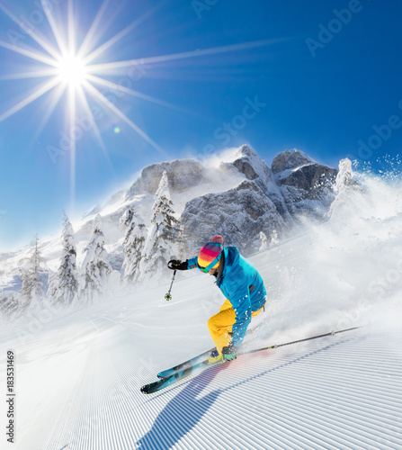 Fotobehang Wintersporten Skier on piste running downhill
