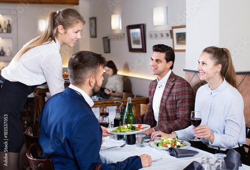 Fototapeta Polite smiling waitress bringing ordered dishes to guests at restaurant obraz na płótnie