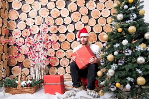 f37c00f5004bc Man in santa hat with red box sit on sledge - Buy this stock photo ...
