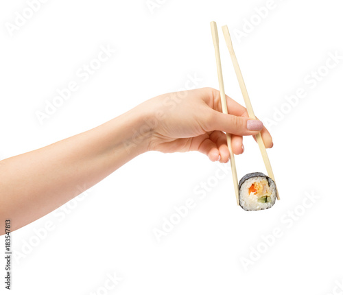 Sushi roll with wooden chopsticks in female hand on white background