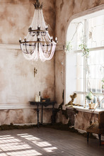 Old Fashioned Vintage Room Corner With Black Table And Candles. Dirty Walls Covered With Fern, Big Crystal Ceiling Light