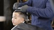 Barber in black gloves cuts hair on the crown of an Asian child, side view 60 fps