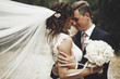 canvas print picture - Groom hugs bride tender while wind blows her veil somewhere in Tuscany, Italy