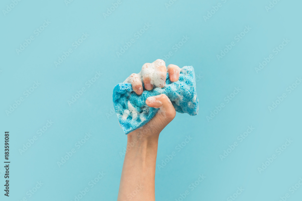 Fototapeta cropped view of hand holding washing sponge with foam, isolated on blue