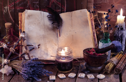 Witch book with pentagram, runes, magic objects and black candle. Occult, esoteric, divination and wicca concept. Mystic and vintage background