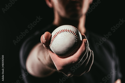 selective focus of man holding baseball ball isolated on black Canvas Print