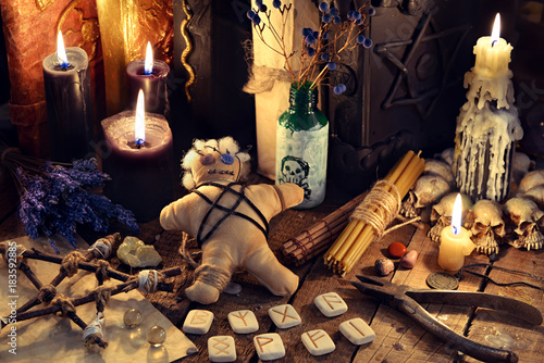 Voodoo doll, black candles, pentagram and old books on witch table. Occult, esoteric, divination and wicca concept. Mystic, voodoo and vintage background