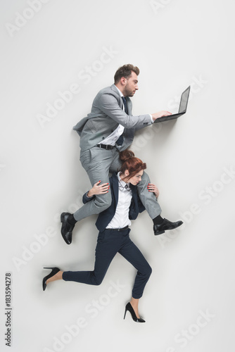 Photo overhead view of businesswoman carrying businessman that working on laptop isola