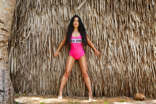 Fotografie, Obraz  Young beautiful brunette girl in front of the huts made of palm leaves on the beach of a tropical island
