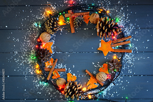 Poster Aromatische Christmas wreath with pine cones, cinnamon, walnuts and dried orange decoration with garland lights and snow on gray wooden background