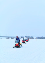 Peopla Riding Snowmobiles On F...