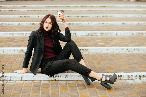 Fotografija  Young fashion hipster business woman student in a suit, sitting on the stairs, steps, drinking coffee