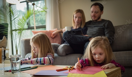 Parents using digital tablet while children drawing a sketch in