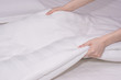 Close up woman hand set up white bed sheet in hotel room