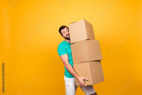 Obraz Concept of courier and messenger service. Grimacing handsome guy is trying to keep big stack of cardboard bosex in his hand, isolated on yellow background - fototapety do salonu
