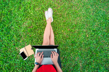 Top View Of A Studient Woman Sitting On The Green Grass In A Park With Laptop, Smart Phone And Book. Phone With Blank