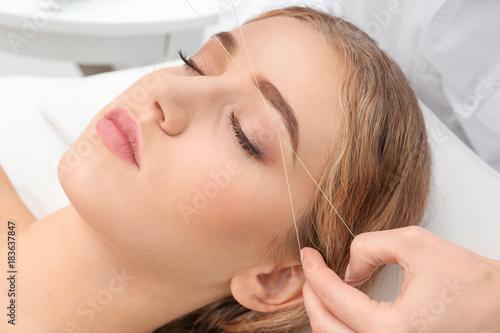 Photo  Young woman having eyebrow correction procedure in beauty salon