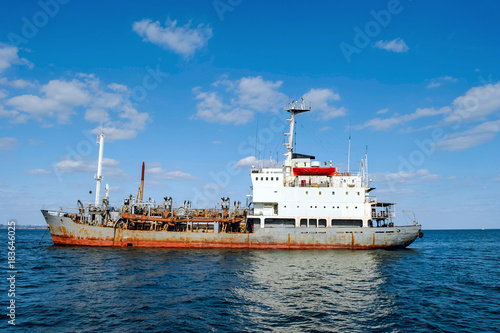 Foto op Canvas Schip Old rusty ship in the blue sea