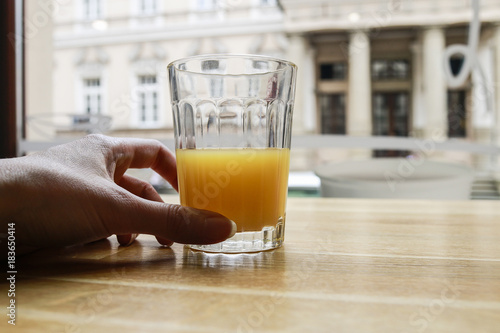 Half full or half empty glass of orange juice by the window