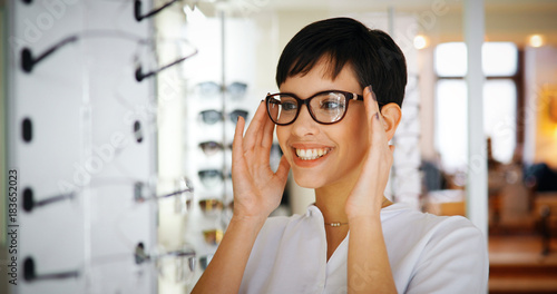 Beautiful woman with optician trying eyeglasses