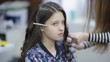 Hairdresser makes the final stage of creating a hairstyle for a cute girl. Professional hairdresser stylist makes a hairstyle for a cute European little girl brunette in a beauty salon