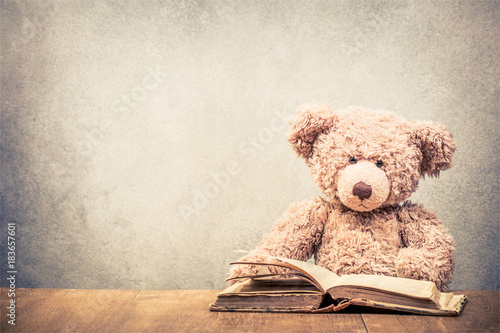 Fototapeta  Retro Teddy Bear toy sitting at the old wooden desk with old book front concrete wall background