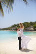 Happy groom holds bride on his hands under wedding ceremony arch on tropical island beach on Maldives. Turquoise ocean lagoon, white sand and bungalows of luxury spa resort on background. Honeymoon.