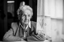 Old Lady Sadly Sitting Near The Window.