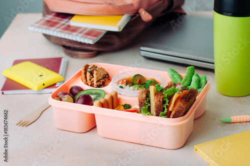 Open lunch box with healthy food on the table near backpack, laptop and thermo mug