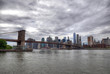 Colorful HDR image of Brooklyn Bridge with the skyline of Downtown Manhattan on cloudy sky