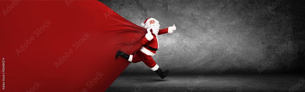 Fototapeta Weihnachtsmann mit einem Sack voller Geschenke!