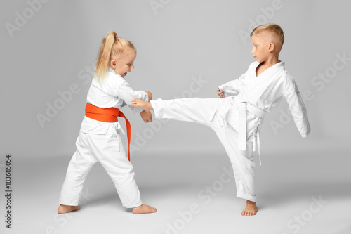 Foto op Canvas Vechtsport Little children practicing karate on light background