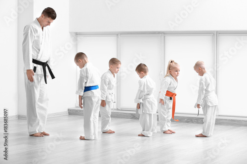 In de dag Vechtsport Little children and instructor performing ritual bow prior to practicing karate in dojo