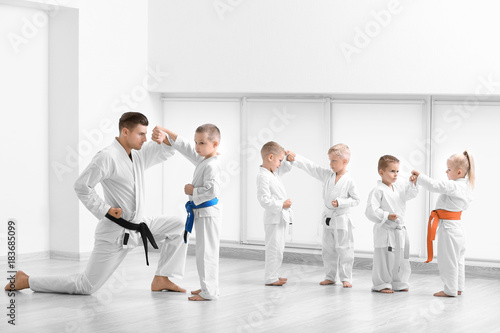 Crédence de cuisine en verre imprimé Combat Little children with instructor practicing karate in dojo