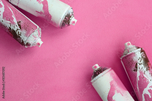 Some used pink aerosol spray cans with paint drips lies on a blanket of soft and furry light pink fleece fabric. Classic female design color. Graffiti hooliganism concept © mehaniq41